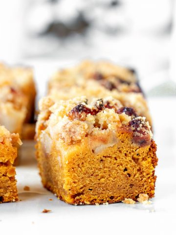 Square of pumpkin cake with apples and crumble, white greyish surface