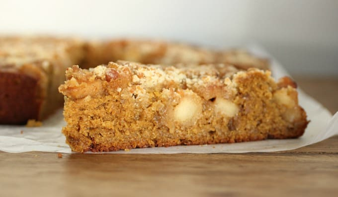 Slice of Pumpkin Apple Crumble Cake on parchment paper on a wooden table