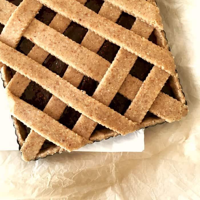 Unbaked lattice square tart on beige parchment paper