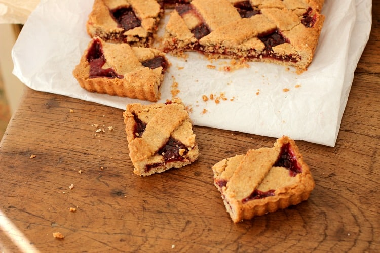 A wooden table with squares of raspberry lattice tart on a white piece of paper