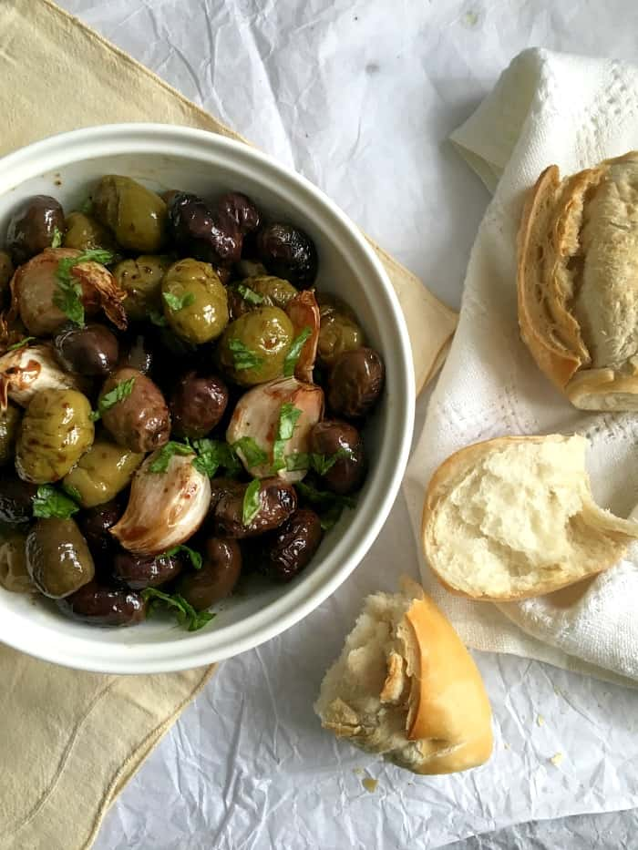 White bowl of Marsala Roasted Olives and Garlic on white surface, bread
