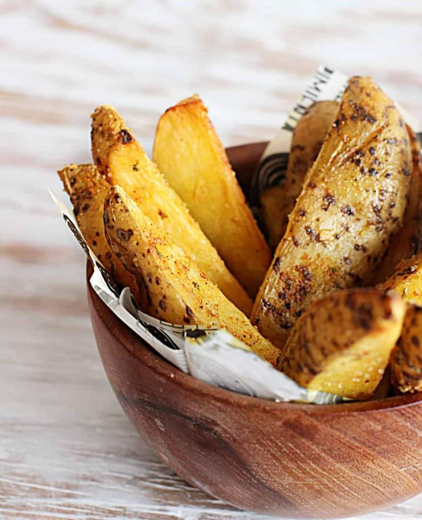 spicy baked potato wedges in wodden bowl on white table