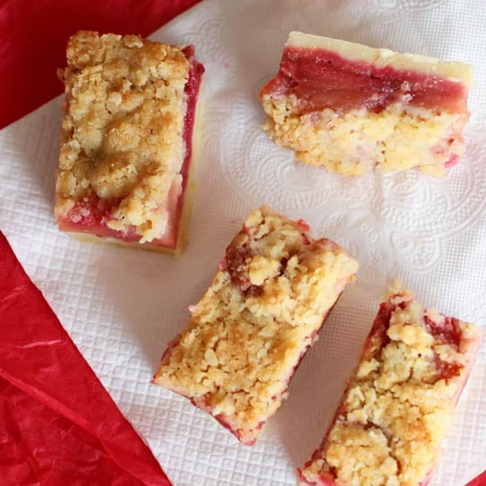 Top view of crumb bars with red filling on a white paper napkin on a red surface