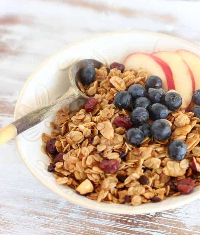 White bowl with Granola, apples and blueberries, on white surface