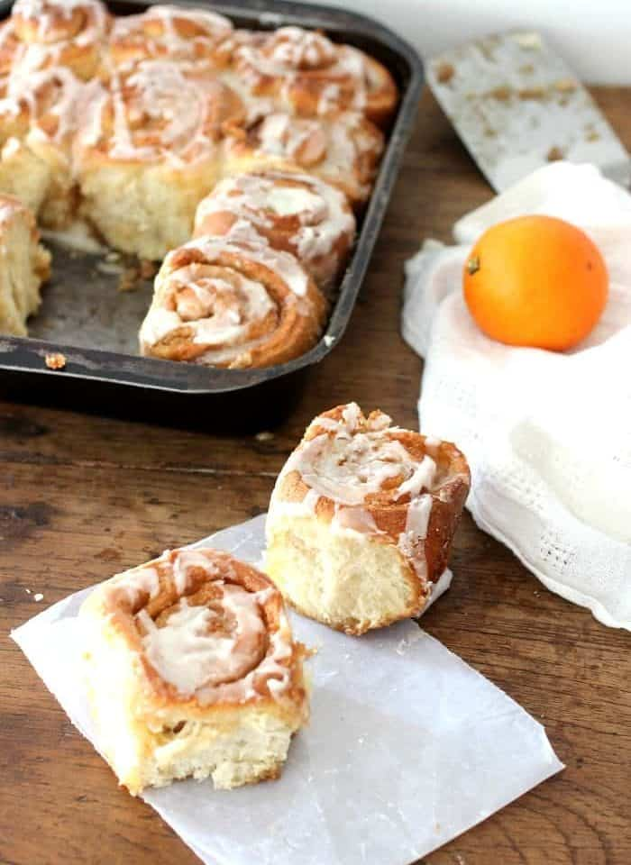 Cinammon rolls on paper on wooden table, rolls in pan, white linen and orange in background