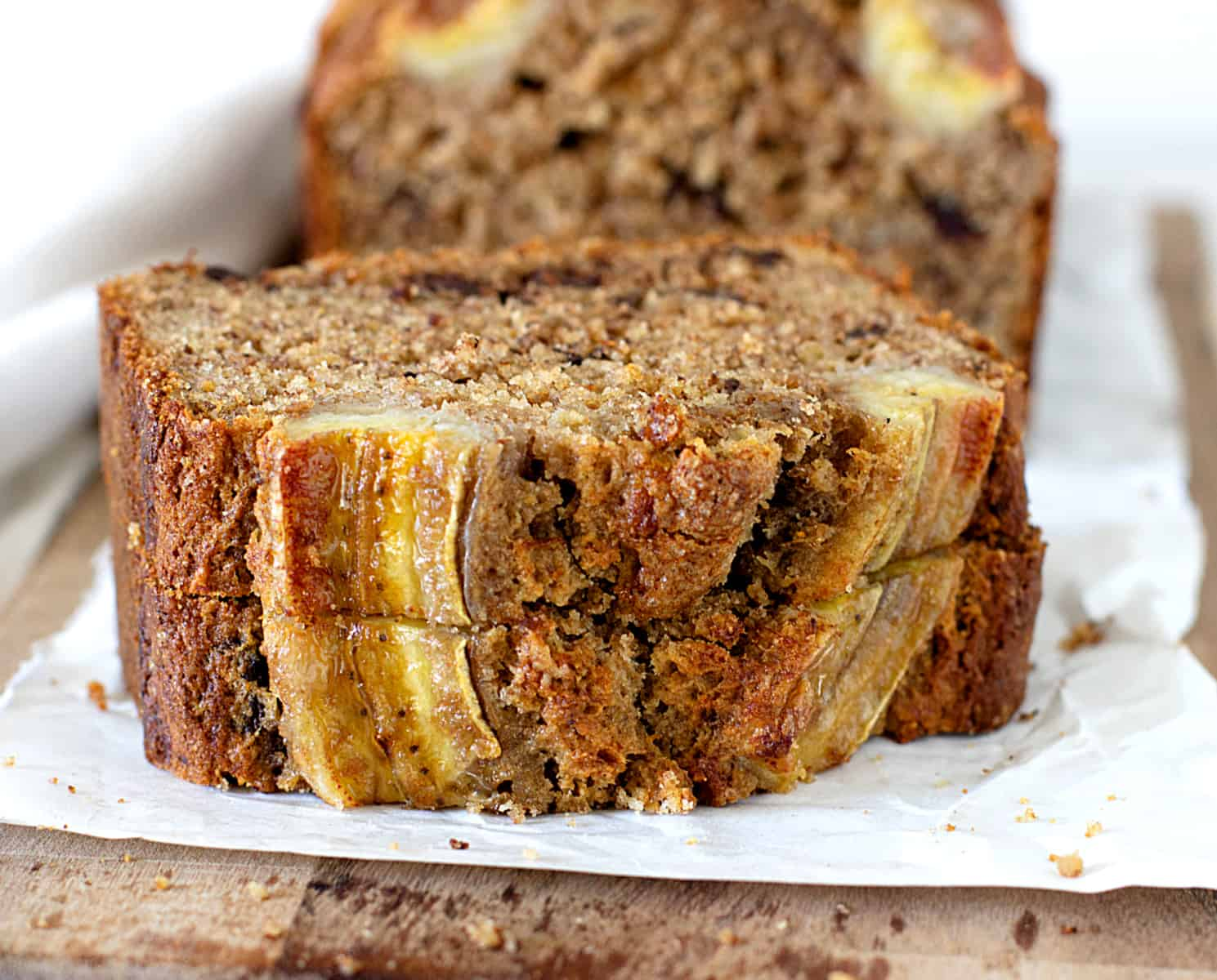 Two stacked slices of Healthier banana bread on white paper