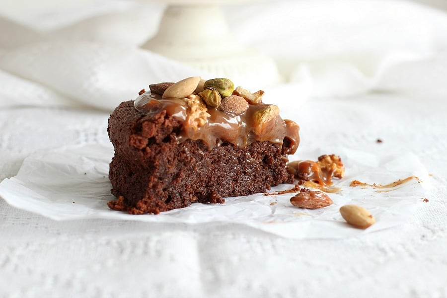 Slice of Flourless chocolate cake on a white linen, nuts and caramel on top