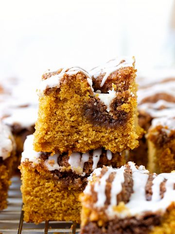 Stacked squares of glazed pumpkin coffee cake on wire rack, white background