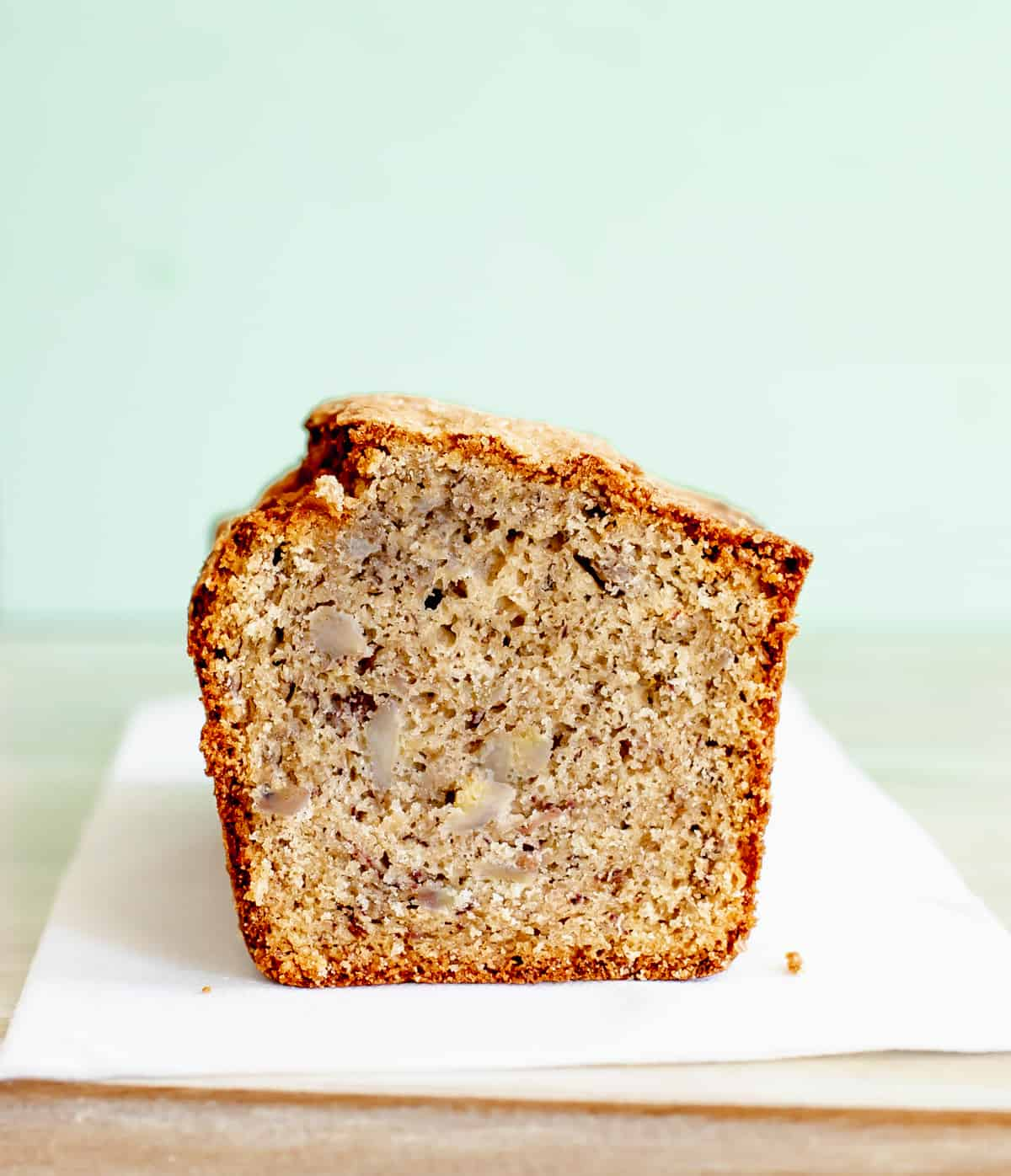 Half loaf of banana bread on beige surface and background