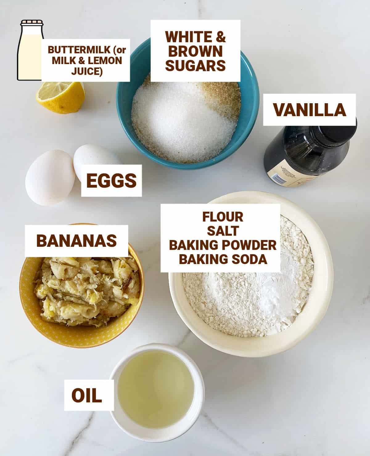 White surface with bowls containing ingredients for banana bread including oil, vanilla, lemon, eggs, sugars, dry ingredients