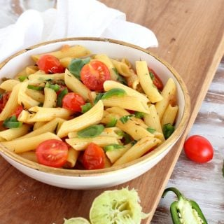 white bowl with pasta and tomatoes on wooden board, white kitchen towel, squeezed limes