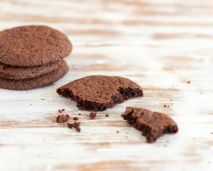 Three chocolate cookies stacked and one eaten on a beige and white table
