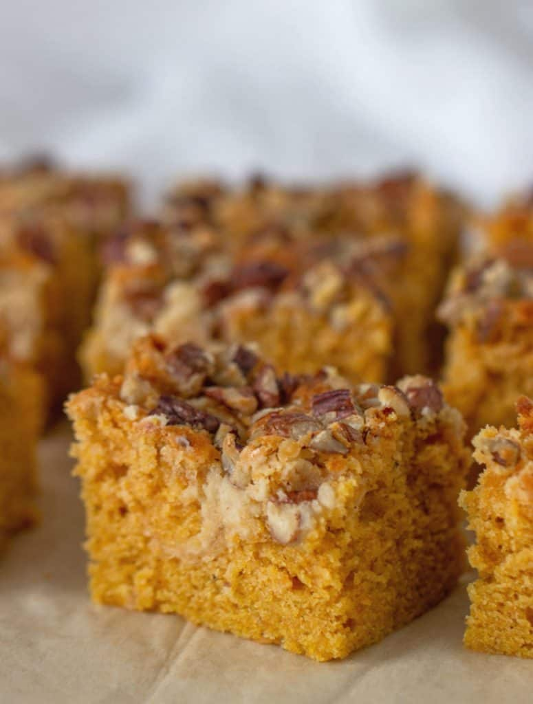 Close-up squares of pumpkin sheet cake, pecan topping, brown paper