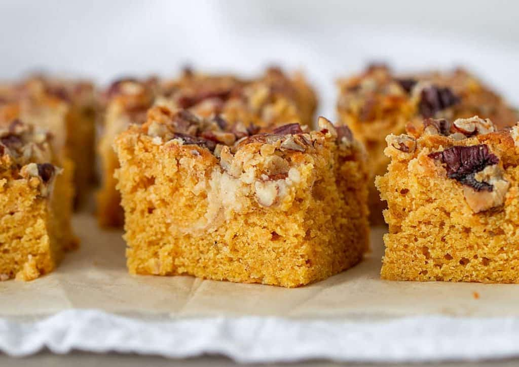 Close-up squares of pumpkin sheet cake, pecan topping, brown paper on white cloth