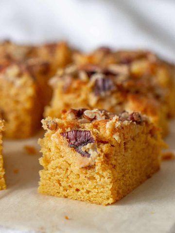 Close-up squares of pumpkin sheet cake, pecan topping, brown paper surface