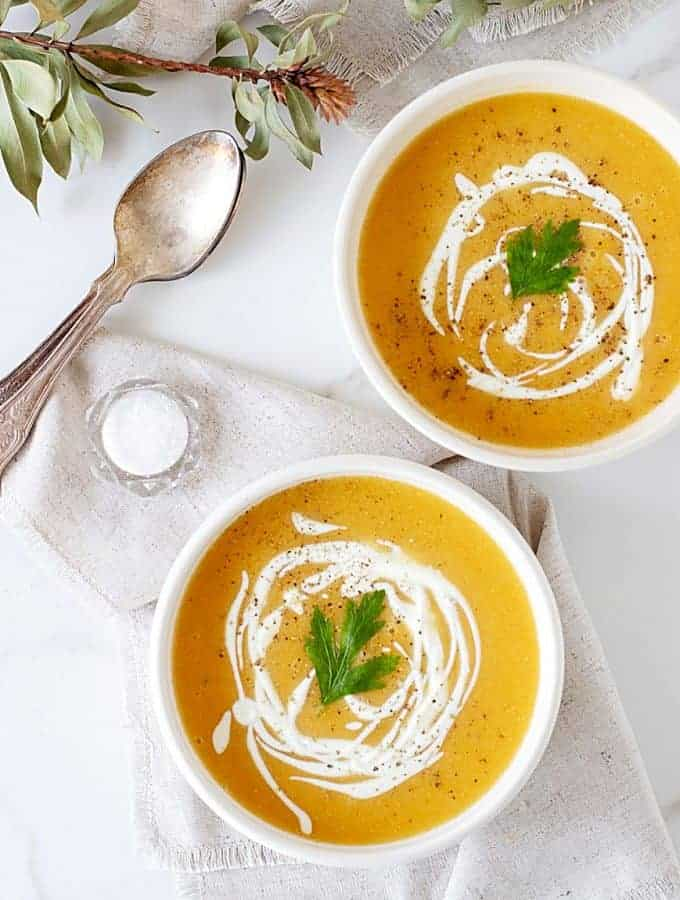 Two white bowls of orange soup, white background, spoons, salt