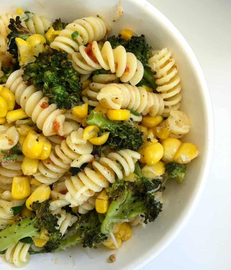 White bowl with broccoli corn harissa pasta