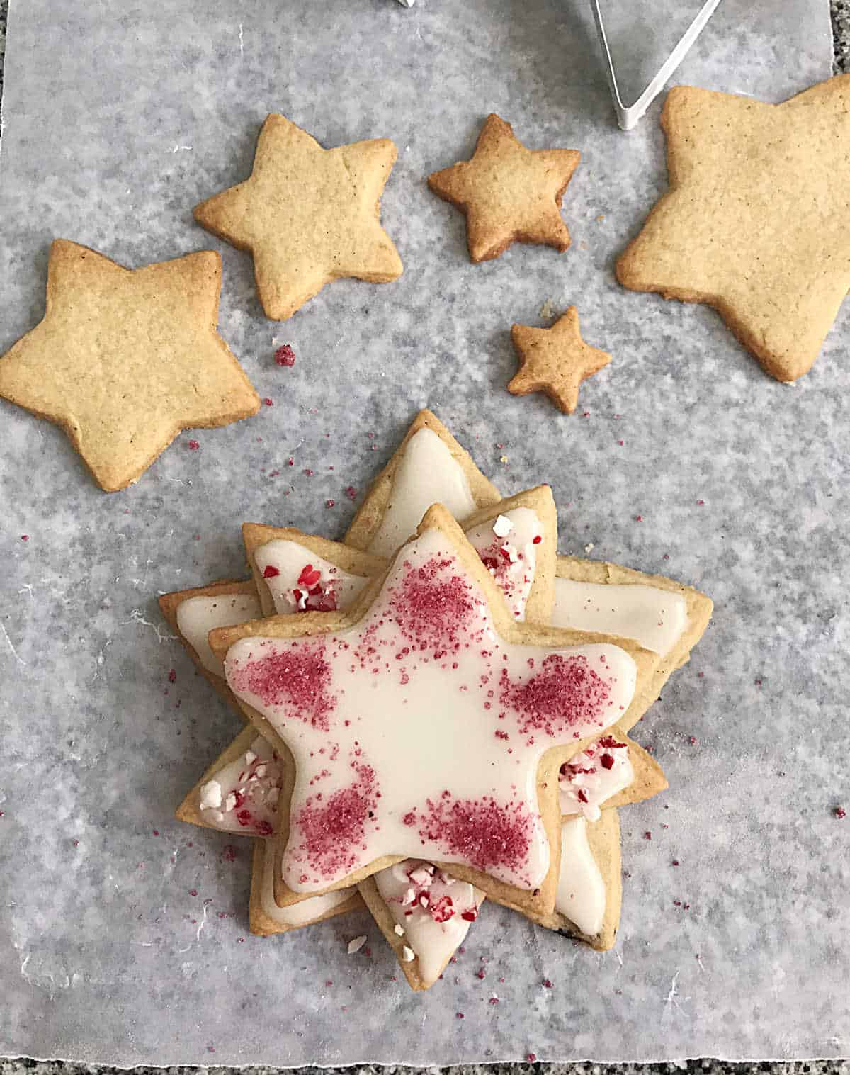 Assembling stacked star shaped cookies with white frosting and crushed candy cane on piece of parchment paper
