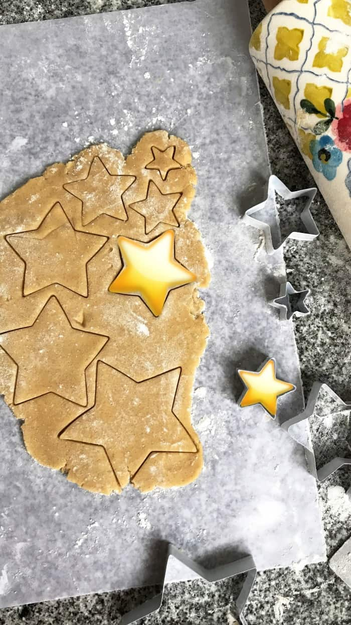 Cutting star shaped cookies on a piece of parchment paper, metal cookie cutters and colorful rolling pin beside