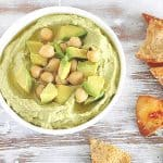 Washed white table with bowl containing avocado dip, chickpeas on top, pita chips around