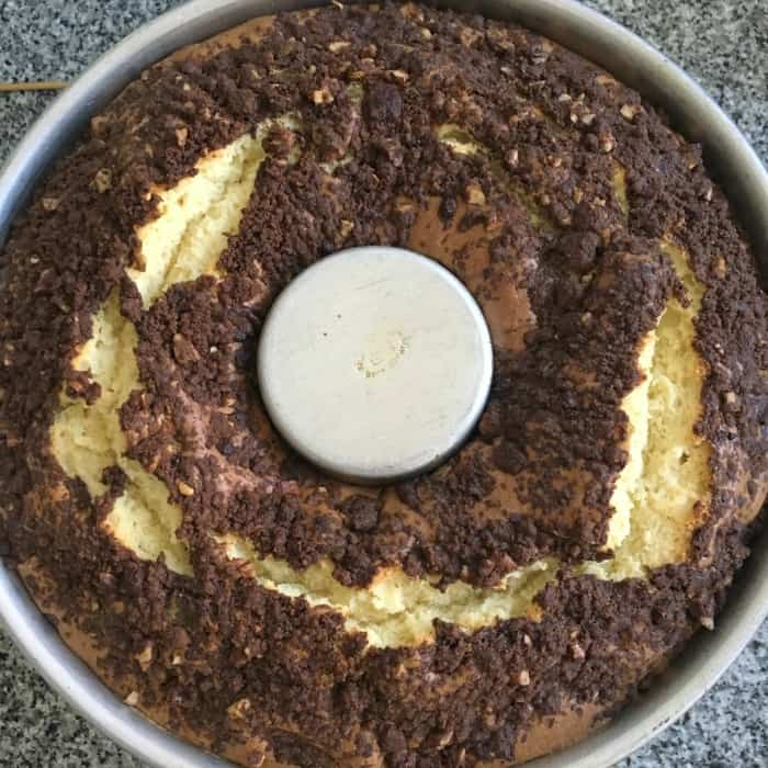 Whole baked streusel topped cake in tube pan on grey surface