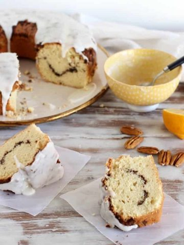 Two slices of cake on white table, rest of cake on plate, bowl with spoon, loose pecans