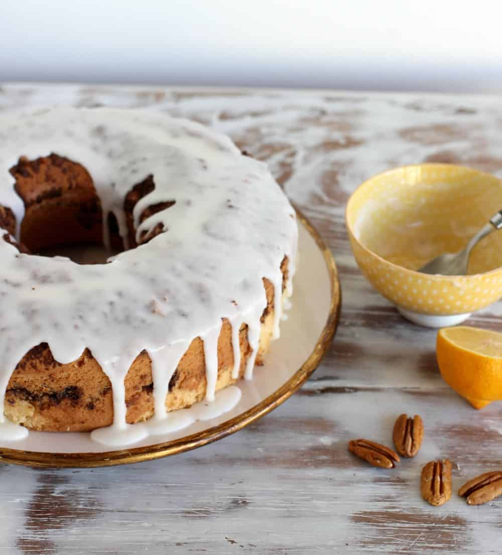 Whole glazed coffee cake on whitish table, yellow bowl, loose pecans
