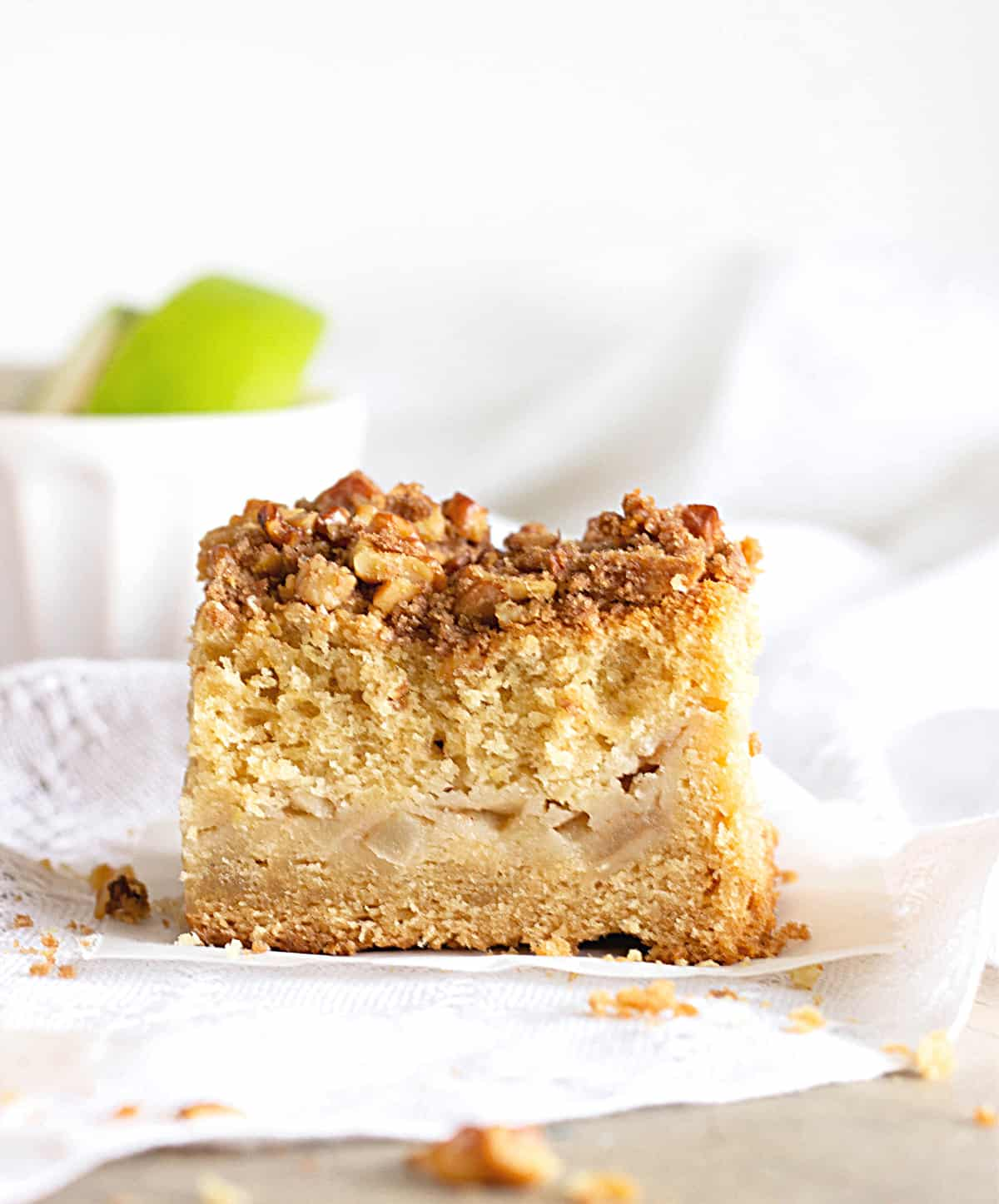 Squares of Apple coffee cake, white surface, white bowl and green apples