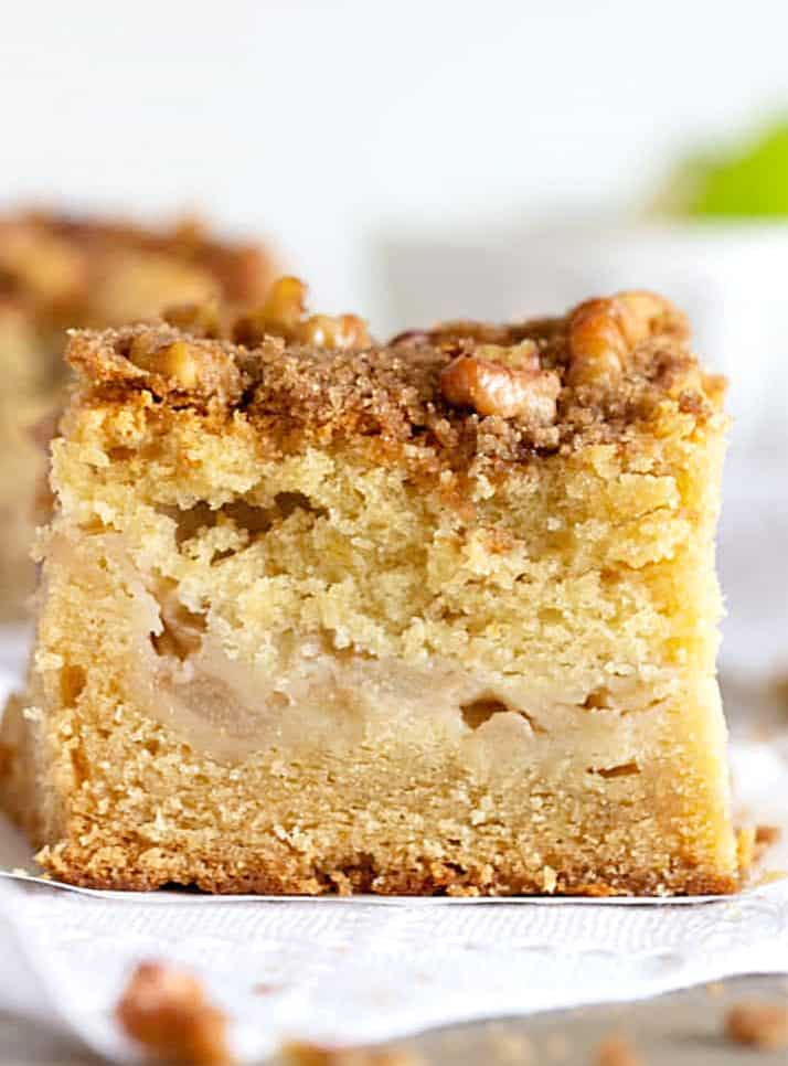 Close-up of Apple cake square with walnut crumble on white napkin