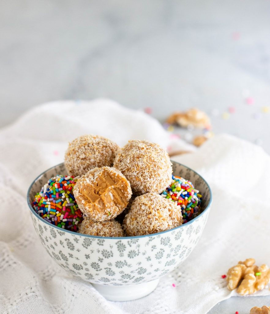 Grey bowl with colorful dulce de leche coconut fudge balls, white cloth