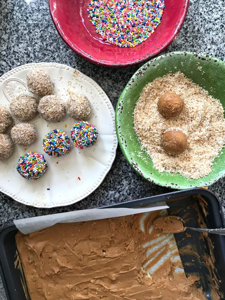 Making dulce de leche fudge balls, colorful bowls with sprinkles, fudge, half-made truffles