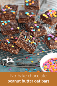 Squares of chocolate no-bake oat bars with confetti on a wire rack