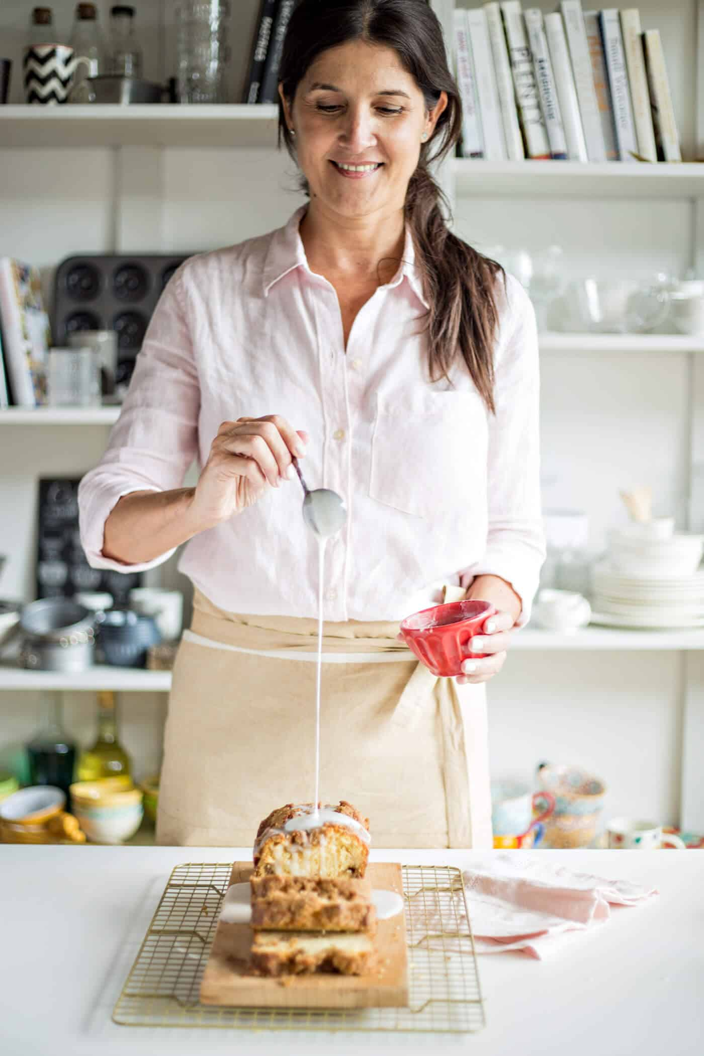 Dark haired woman with pink shirt and beige apron pouring glaze over cake, bookshelf beneath her