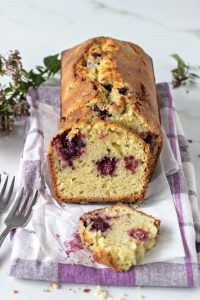 Slices and whole Orange blackberry muffin loaf, kitchen towel, forks, small flowers