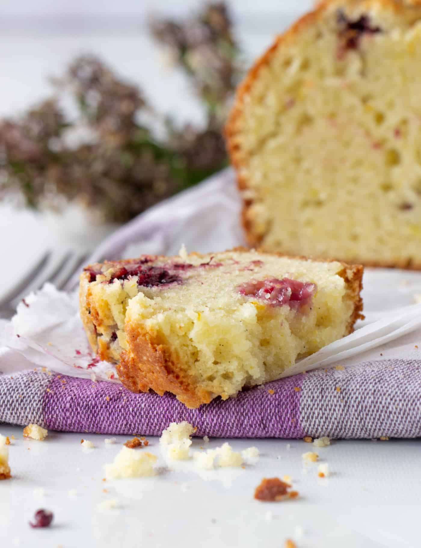 Close-up slice and loaf of Orange blackberry muffin cake, checkered kitchen cloth