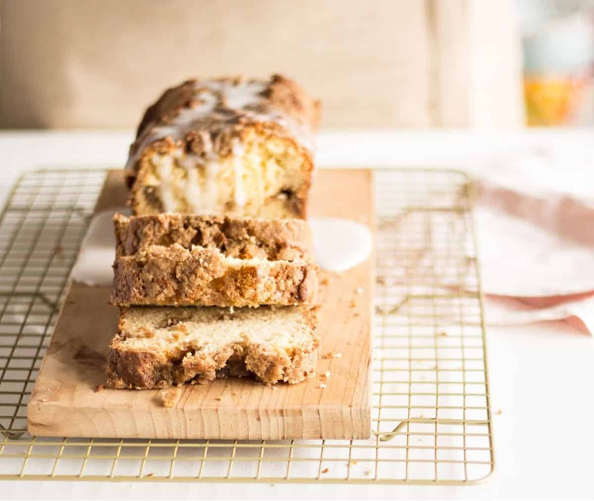 Metal rack with glazed coffee cake loaf on a wooden board, pink napkin beside it