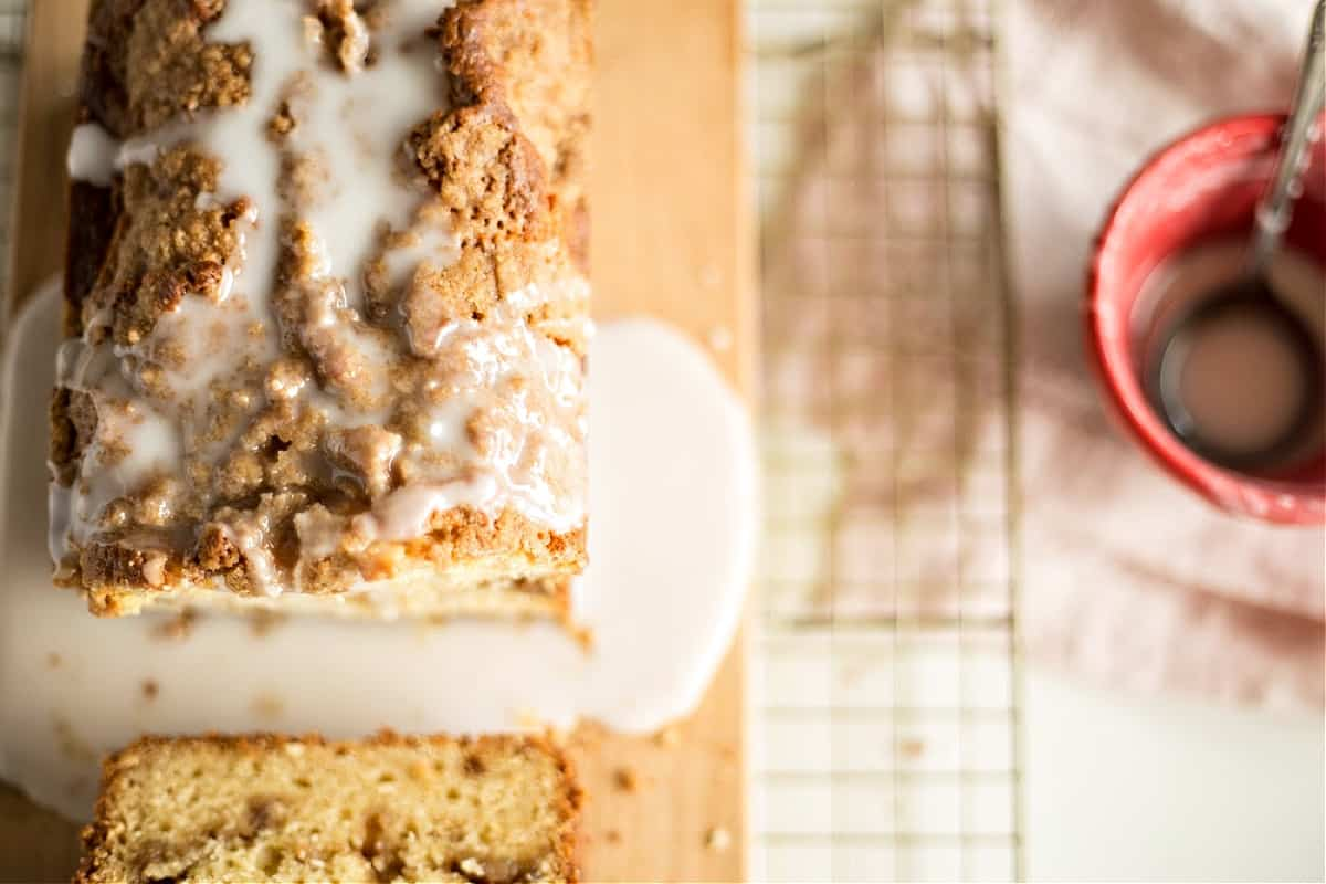 Top view of loaf cake drenched in sugar glaze, metal rack on white surface, red bowl