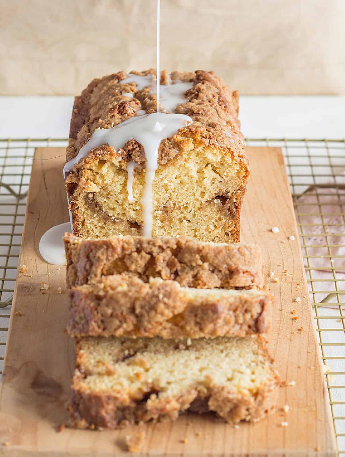 Glaze pouring over coffee cake loaf on a wooden board, metal rack
