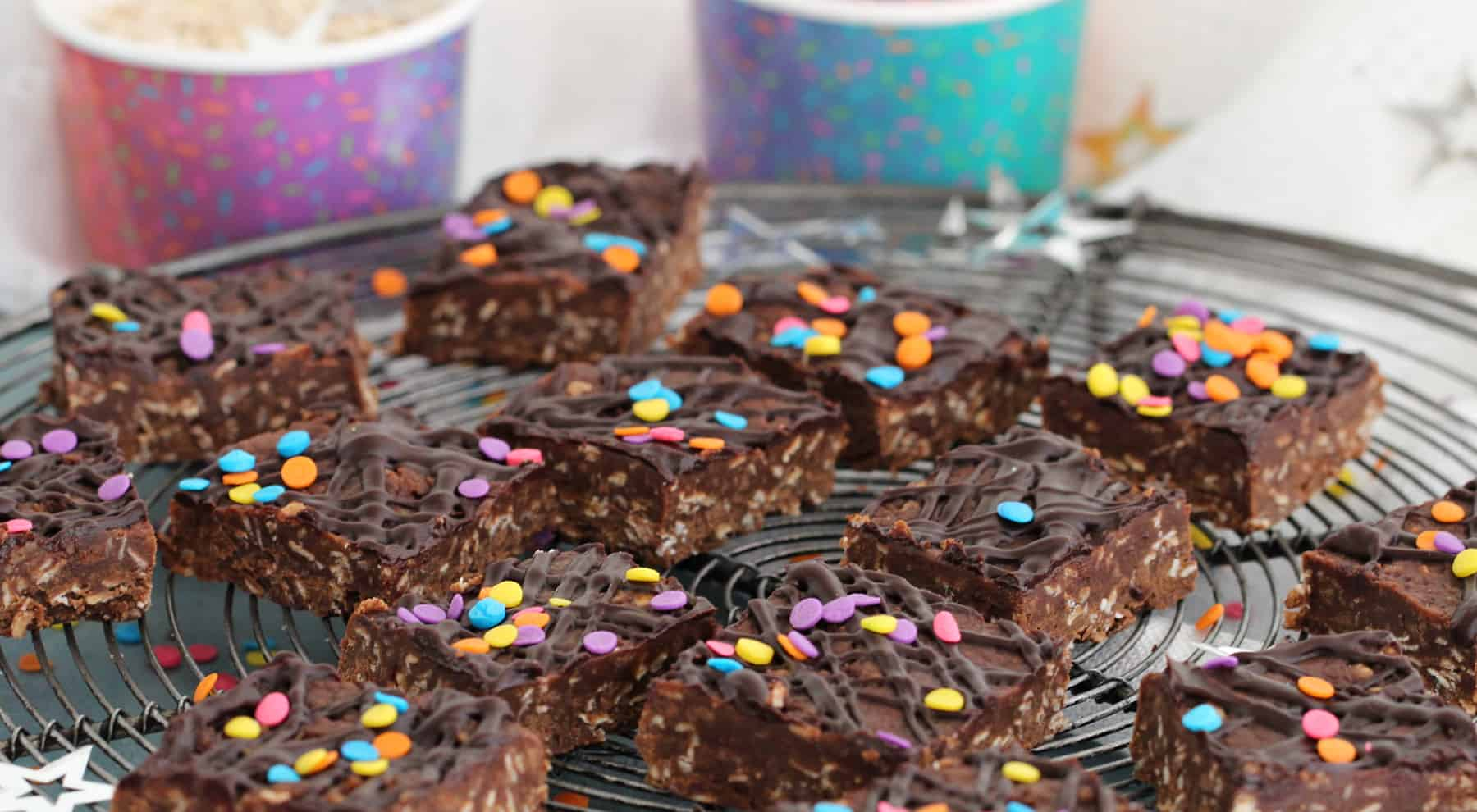 No-bake chocolate peanut butter cookie oat bars on wire rack, paper cups, confetti