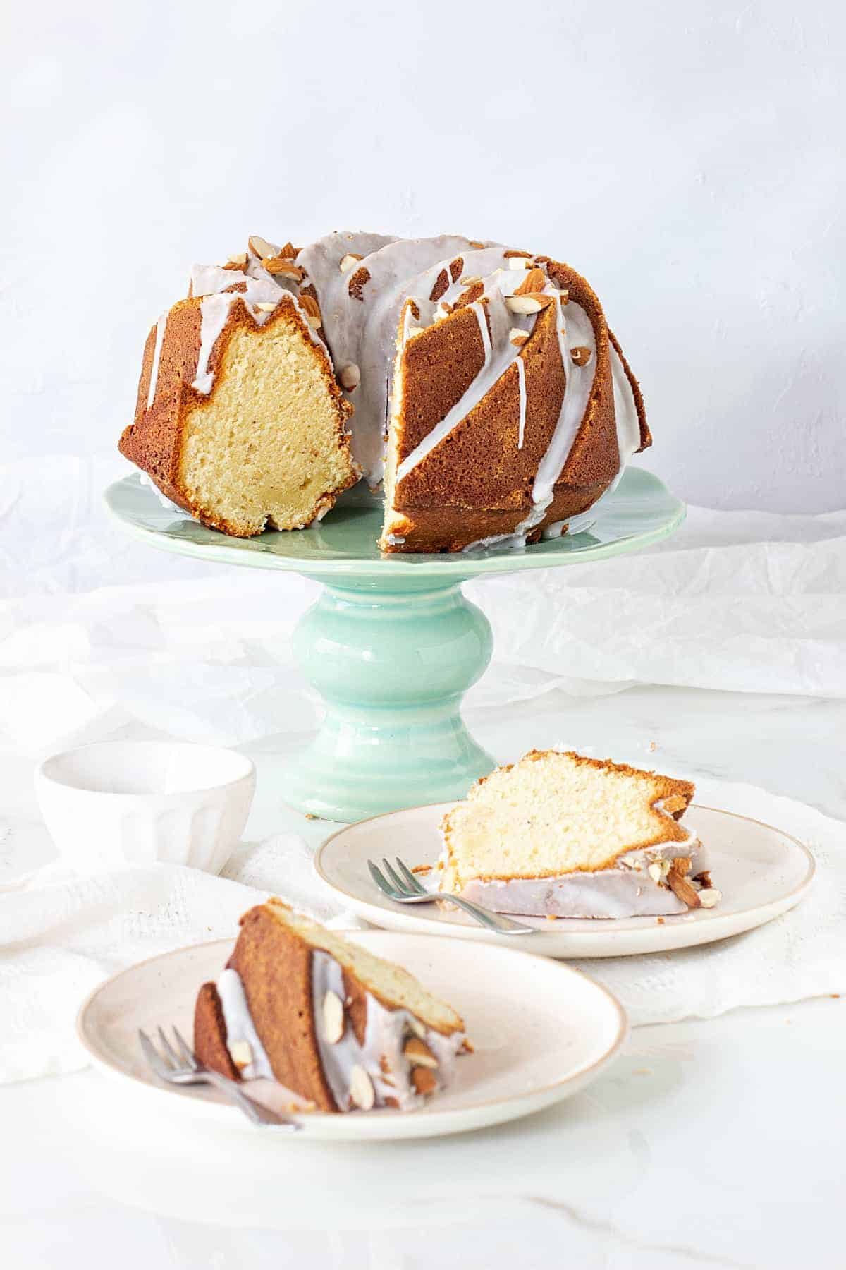 Bundt cake on a green cake stand, two slices on plates, forks, white surface