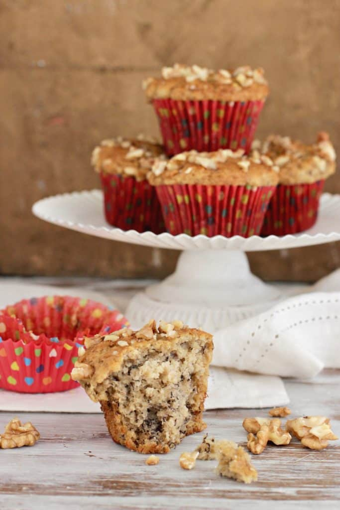 Healthier banana muffins on cake stand, half on table, red paper liners