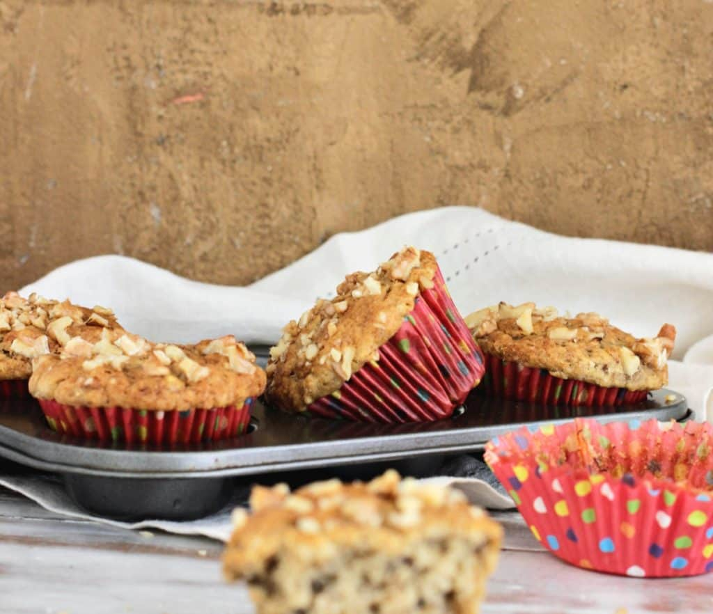 Healthier banana muffins in pan, polka dot red paper liners, light brown background