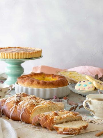 An Easter brunch table with a pie on a stand, cookies, braided breads, a lemon ricotta pie.