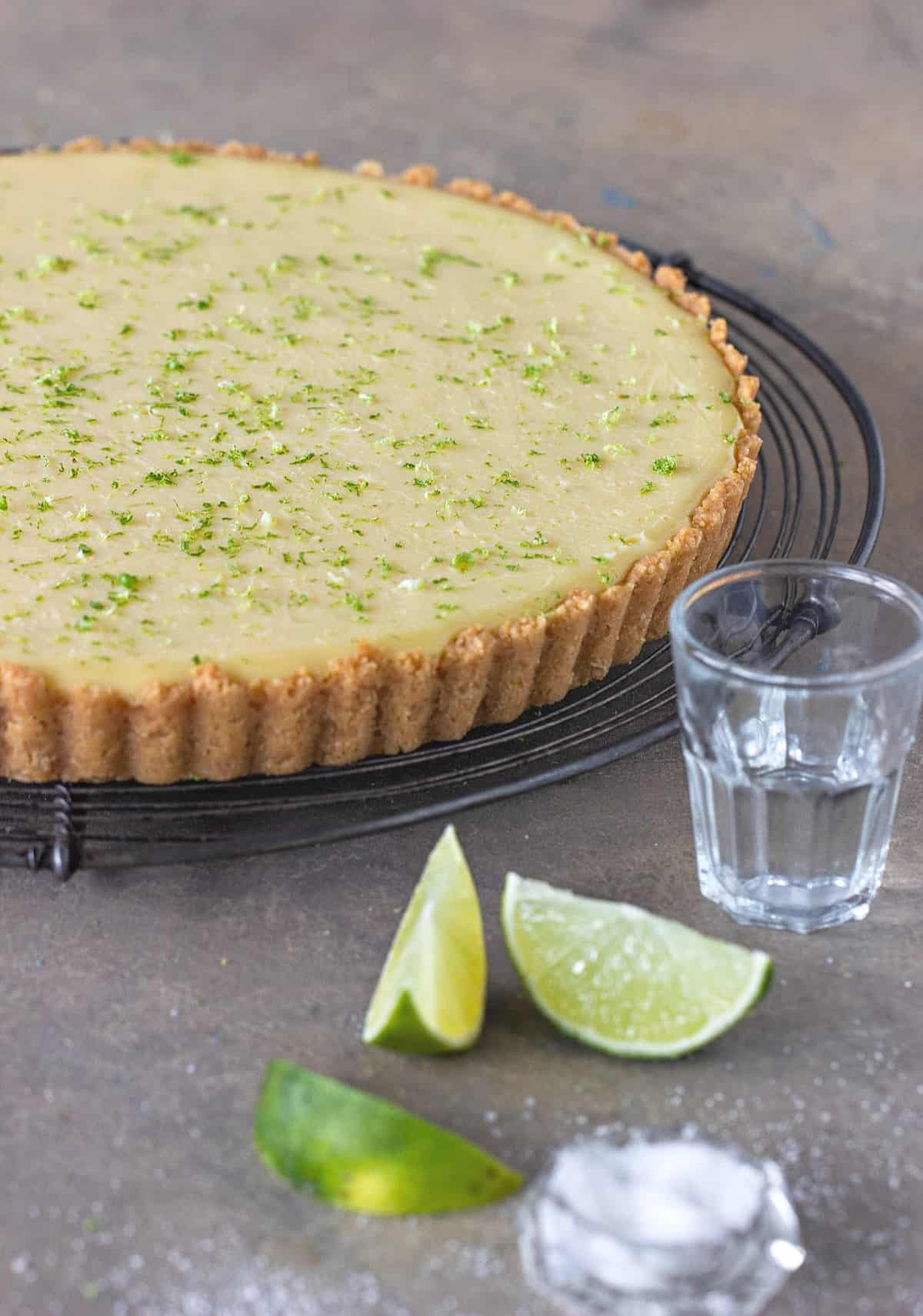 Whole margarita lime pie with tequila shot and lime wedges