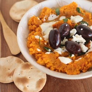 Bowl of carrot dip, black olives, goat cheese and crackers