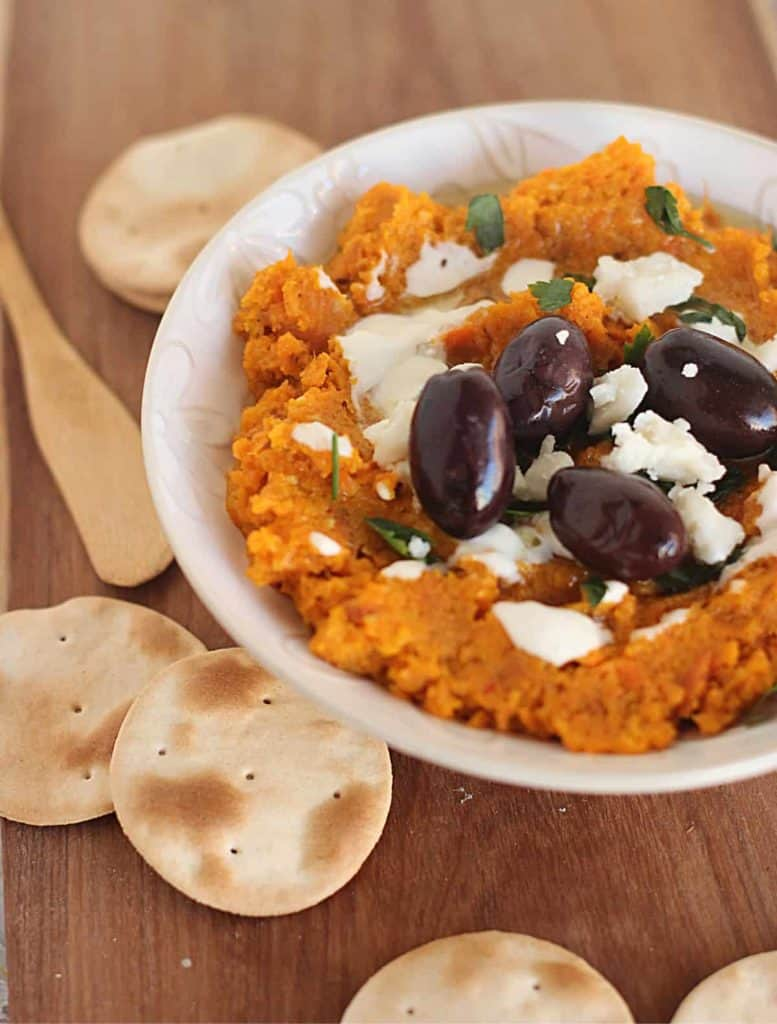White Bowl of carrot dip, black olives, goat cheese and crackers on wooden board