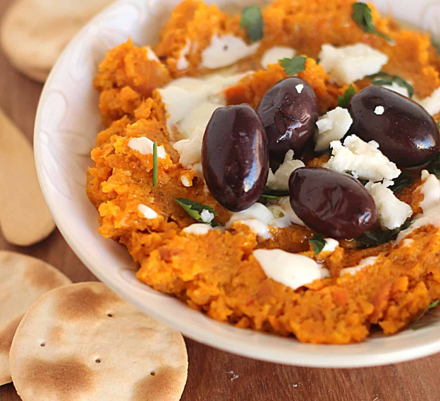 White Bowl of carrot dip, black olives, goat cheese and crackers