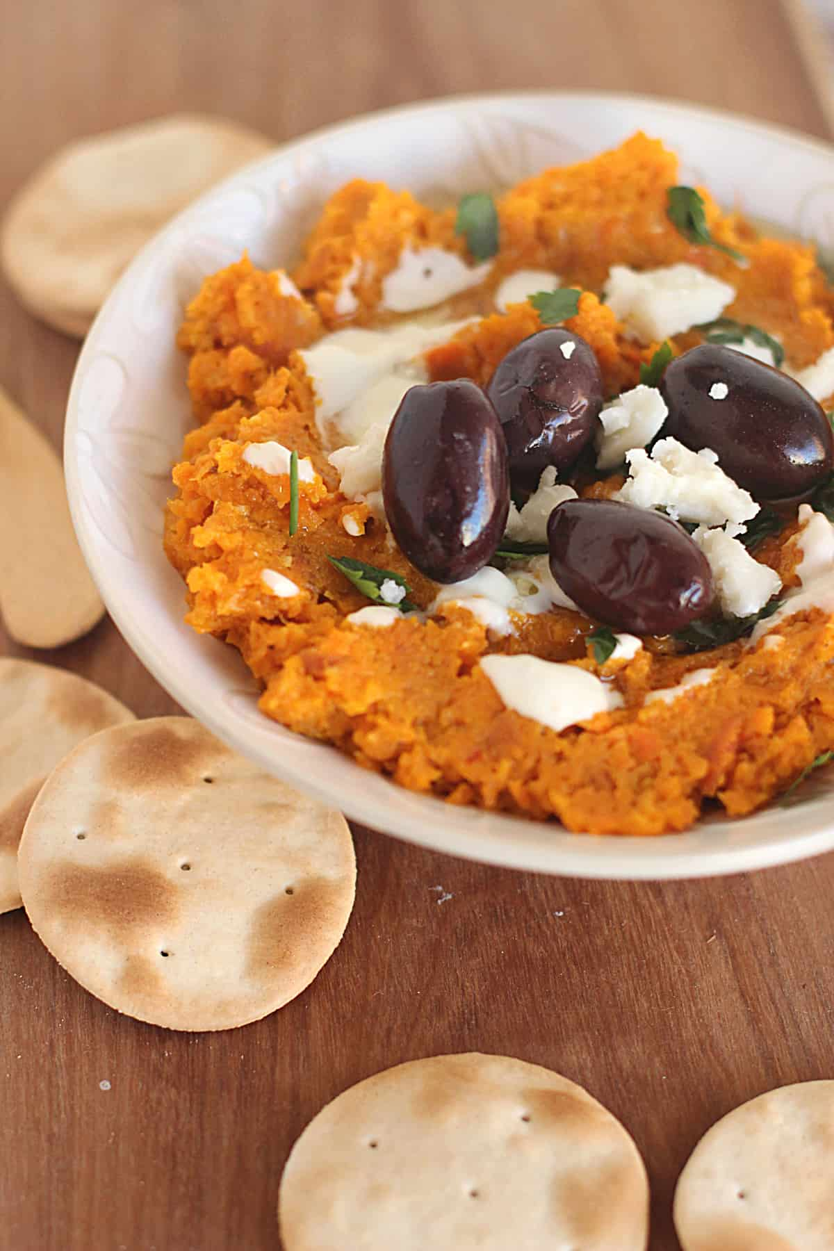White Bowl of carrot dip, black olives and crackers on wooden board