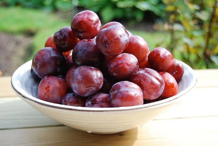 White bowl of whole red plums on a table