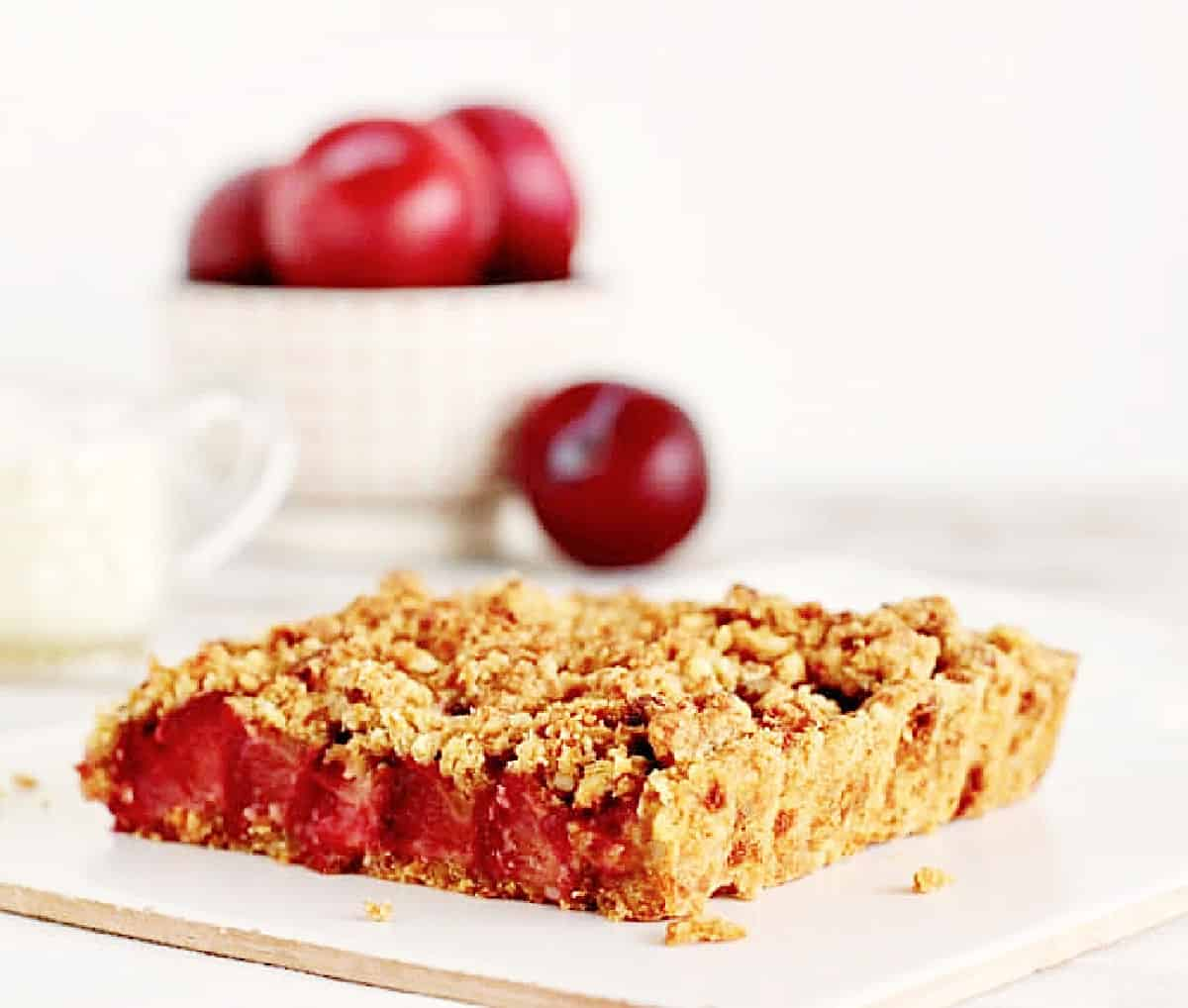 One square serving of plum crumble tart on white surface; whole plums in bowl in background